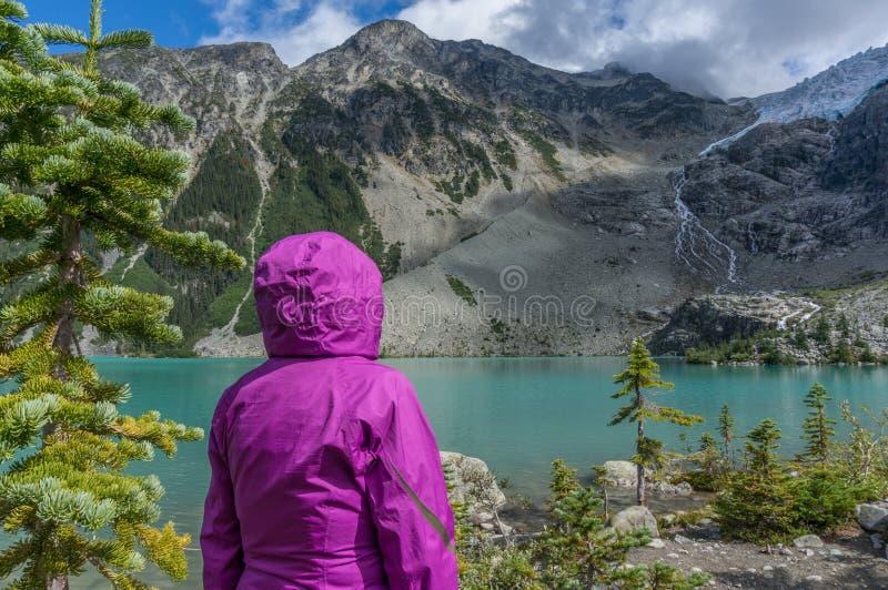 Kobieta w purpura deszczu kurtce przy Halnym jeziorem zdjęcie royalty free