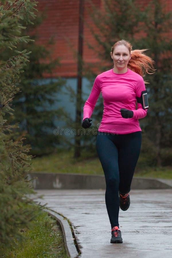 Kobieta w różowym bieg w jesień parku Żeński biegacz plenerowy, Zdrowy styl życia obrazy stock