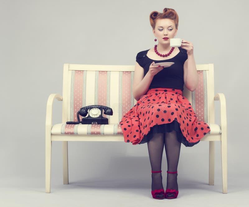 kobieta w retro stylu pije kawowego obsiadanie na fotografia royalty free