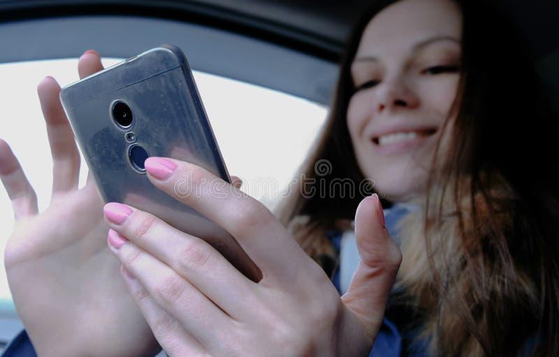 Kobieta w samochodzie z telefonem komórkowym Młoda piękna brunetki kobieta patrzeje coś w telefonie komórkowym i śmiechach i zdjęcia royalty free