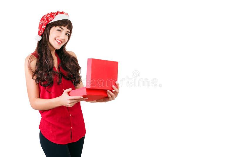 Kobieta w Santa kapeluszowego otwarcia prezenta Bożenarodzeniowym pudełku odizolowywającym na bielu z copyspace Szczęśliwa dziewc fotografia royalty free