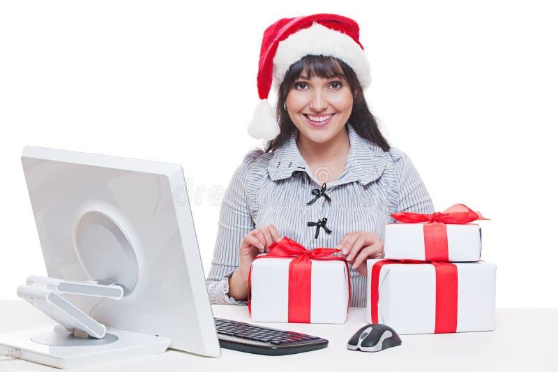 Kobieta w Santa kapeluszu robi bożych narodzeń prezentom fotografia royalty free