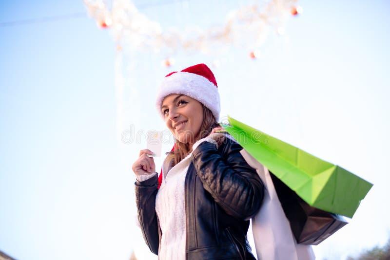 Kobieta w Santa kapeluszu z torba na zakupy zdjęcia royalty free
