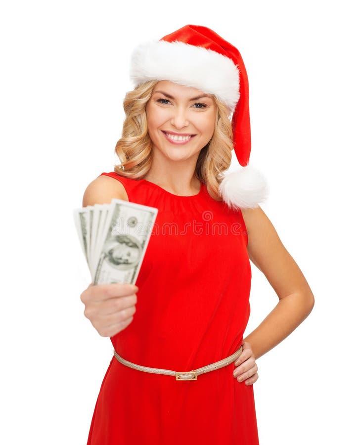 Kobieta w Santa pomagiera kapeluszu z dolara amerykańskiego pieniądze zdjęcie stock