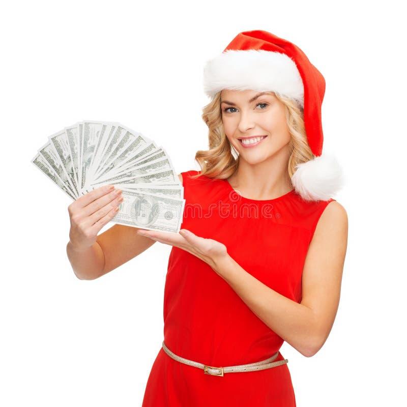 Kobieta w Santa pomagiera kapeluszu z dolara amerykańskiego pieniądze fotografia stock