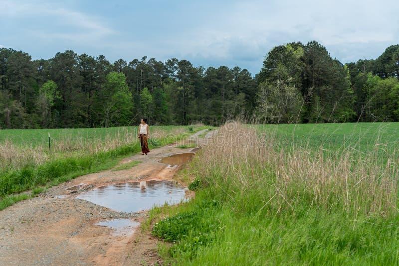 Kobieta w sarongu odprowadzeniu na drodze gruntowej z kałużami w polu fotografia stock