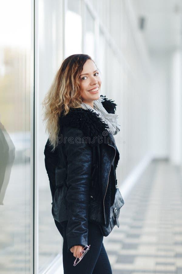 Kobieta w skórzanej kurtce, czarni cajgi pozuje przed odzwierciedlającymi okno Żeński mody pojęcie plenerowy Bielu ścienny tło obrazy stock