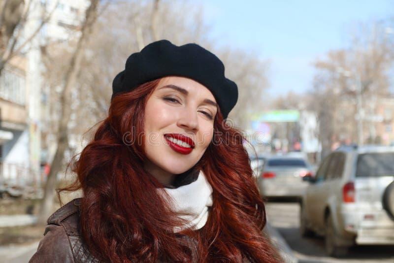 Kobieta w skórzanej kurtce i berecie ono uśmiecha się na ulicie zdjęcie stock