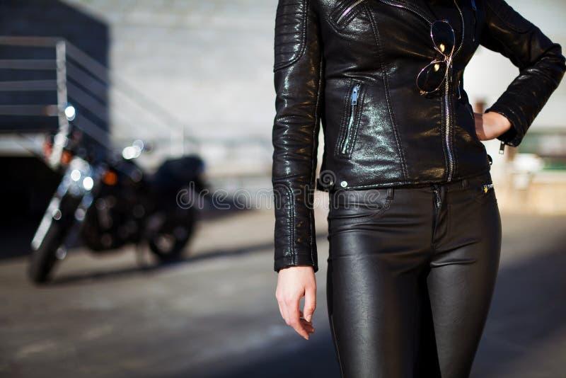 Kobieta w skórzanej kurtki pozycji przed motocyklem obrazy royalty free