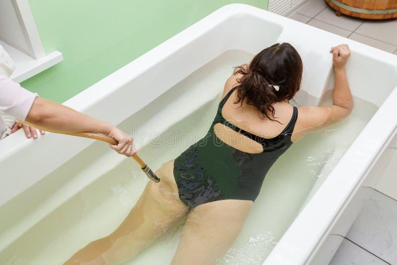 Kobieta w skąpaniu podczas hydromassage w piękno zdroju salonie obraz stock