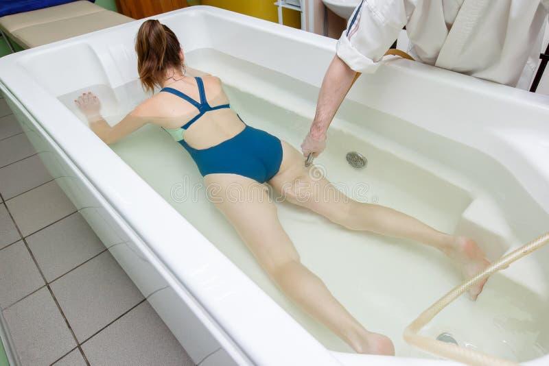 Kobieta w skąpaniu podczas hydromassage w piękno zdroju salonie obrazy stock