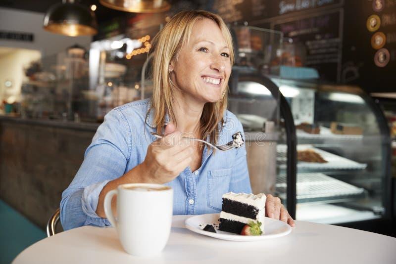 Kobieta W sklep z kawą obsiadaniu Przy Stołowym łasowanie plasterkiem tort fotografia royalty free