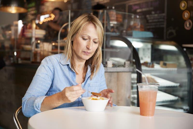 Kobieta W sklep z kawą obsiadaniu Przy Stołowym łasowanie pucharem polewka zdjęcie stock