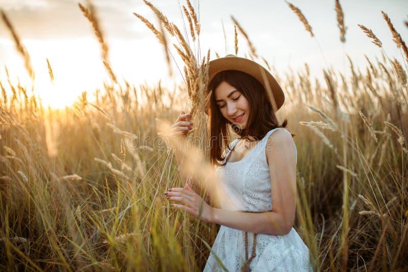 Kobieta w smokingowym i słomianym kapeluszu trzyma pszenicznego bukiet obraz stock