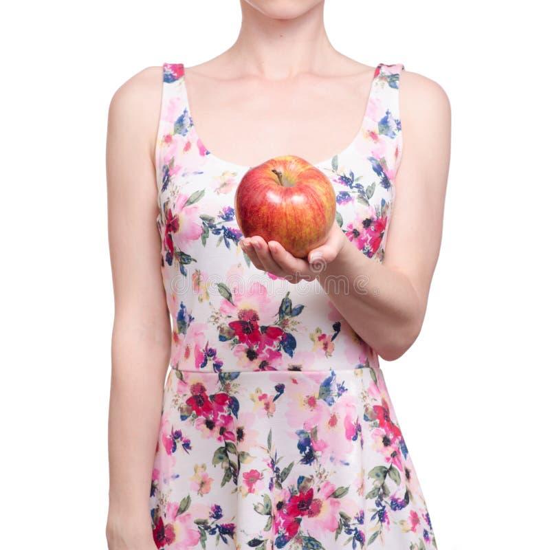 Kobieta w smokingowym kwiecistym druku w ręki owoc jabłku obraz stock