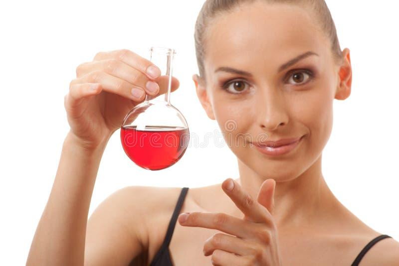 Kobieta w sportach nadaje się chwyty kolbiastych z czerwonym cieczem zdjęcia royalty free
