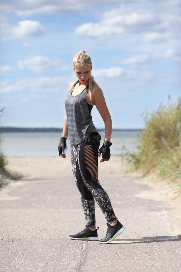 Kobieta w sportswear pozyci przy plażą obrazy royalty free