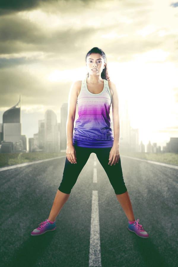 Kobieta w sportswear pozycji na drodze zdjęcia royalty free