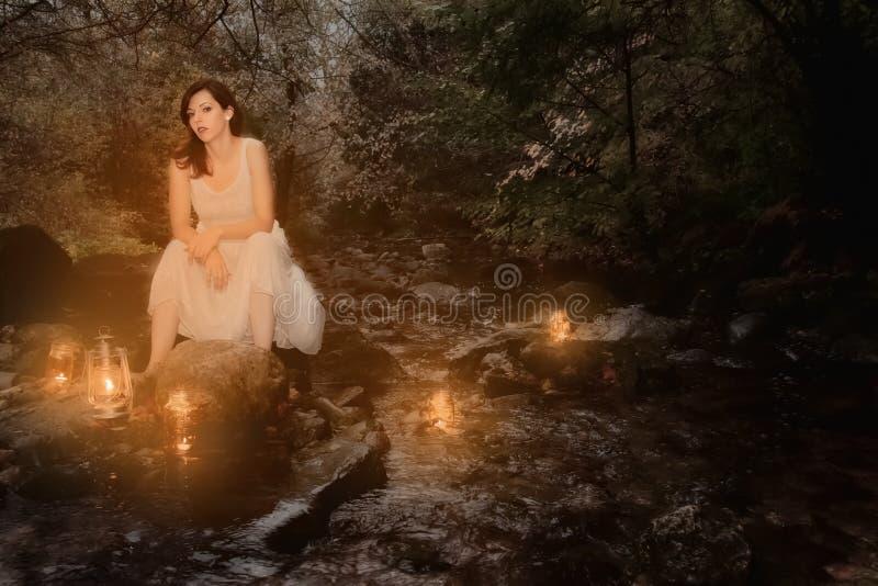 Kobieta w strumieniu z świeczkami zdjęcia royalty free