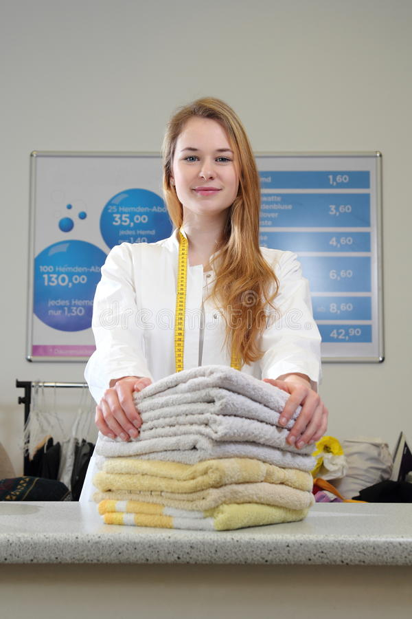 Kobieta w suchym cleaning z ręcznikami na kontuarze zdjęcie stock
