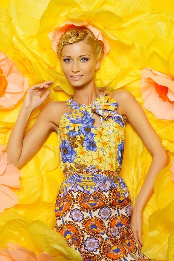 Kobieta w sukni wśród dużych żółtych kwiatów obraz royalty free