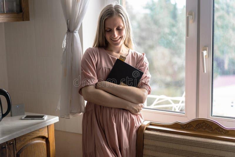Kobieta w sukni z długie włosy stoi przy okno i trzyma książkę w ona ręki i ono uśmiecha się fotografia royalty free