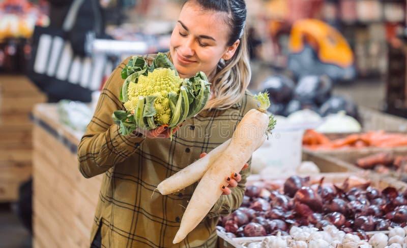Kobieta w supermarkecie Piękna młoda kobieta trzyma świeżych organicznie warzywa, kapusty i rzodkwi, zdjęcia royalty free