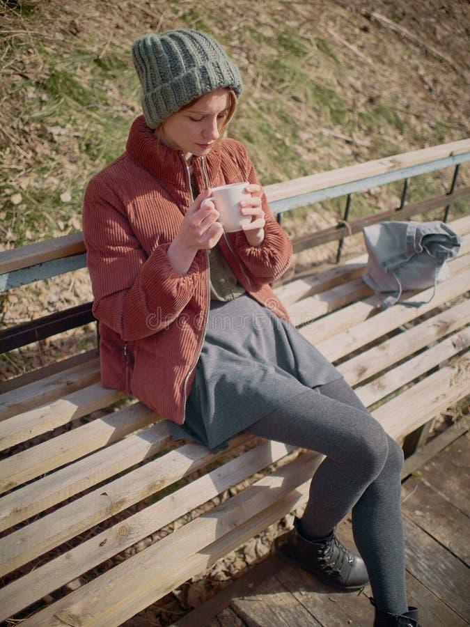 Kobieta w szarym pantyhose i sp?dnicie, b?d?cy ubranym zielonego kapelusz i czerwon? kurtk?, siedzi na ?awce i pije herbaty zdjęcie stock
