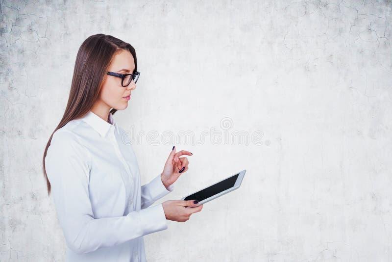 Kobieta w szkłach z pastylką, betonowa ściana zdjęcie royalty free