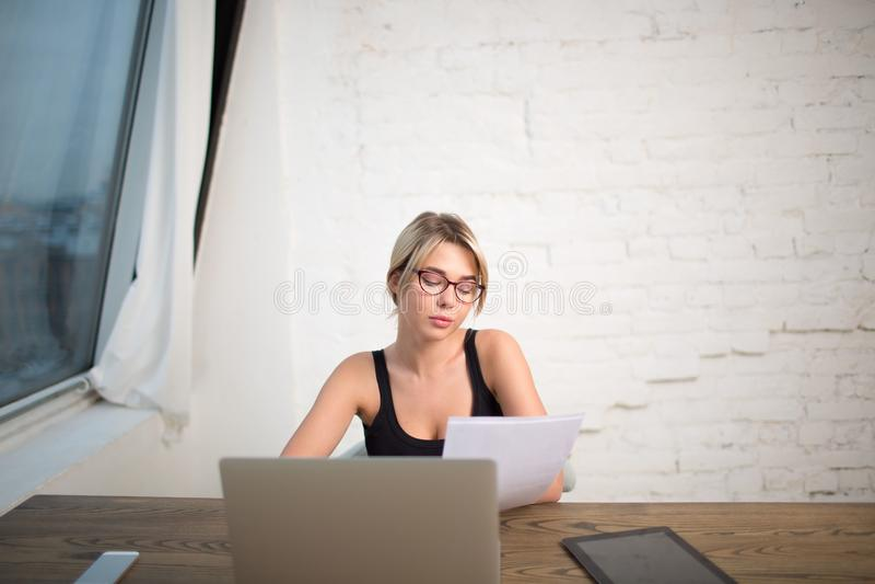 Kobieta w szkło wykwalifikowanego kierownika czytelniczym streszczeniu, siedzi w biurowym wnętrzu obraz royalty free