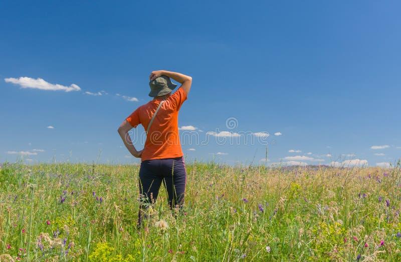 Kobieta w treningów ubraniach podziwia lata dzikiego pole obraz royalty free