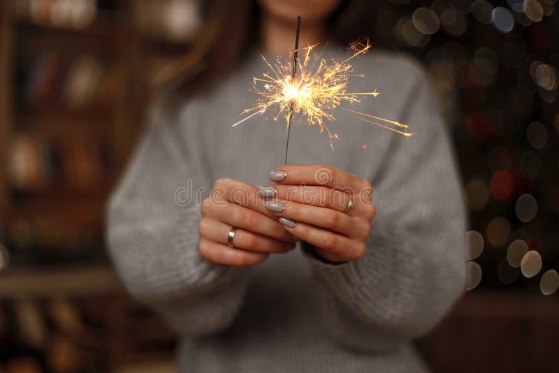 Kobieta w trykotowym pulowerze świętuje wakacje z zadziwiającymi sparklers w żeńskich rękach Zakończenie obraz stock