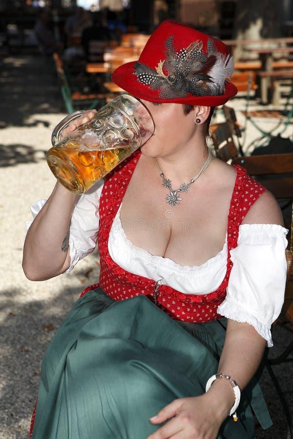 Kobieta w typowym bavarian kostiumu pije piwo obraz royalty free