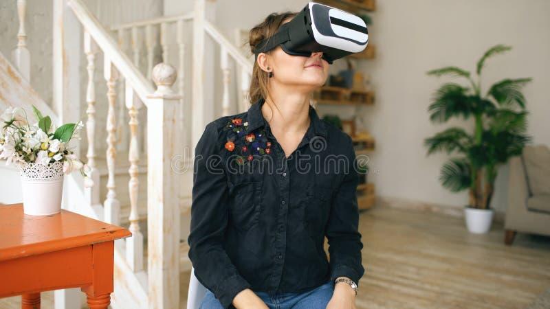 Kobieta w VR słuchawki przyglądający up dotykać przedmioty w rzeczywistości wirtualnej w domu i próbować indoors fotografia royalty free