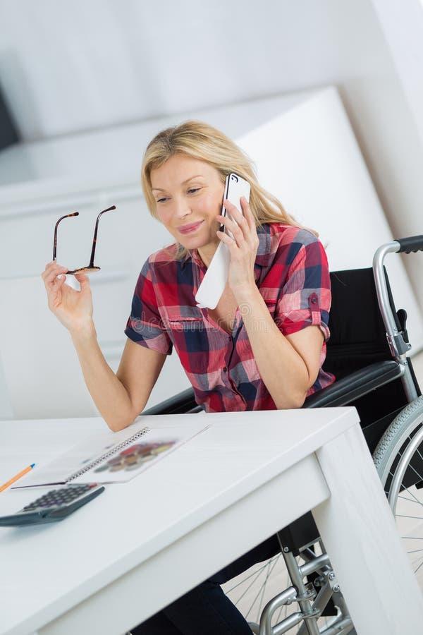 Kobieta w wózka inwalidzkiego robić wzywał telefon komórkowego w domu zdjęcia stock
