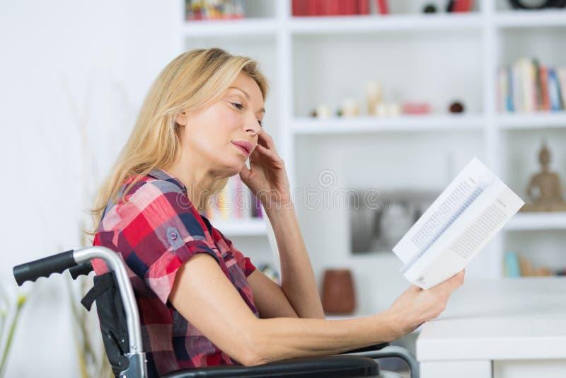 Kobieta w wózku inwalidzkim z książką w domu obrazy royalty free