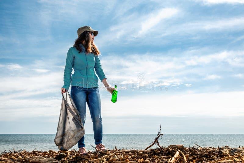 Kobieta w wigili? wakacyjnego ziemskiego dnia zapewnia ochotnicz? pomoc w czy?ci? obszar przybrze?nego gruzy Ziemski dzie? i zdjęcia stock