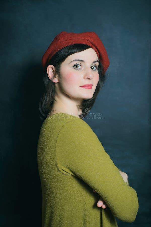 Kobieta w zieleń smokingowym i czerwonym berecie na czarnym ściennym tle zdjęcie royalty free