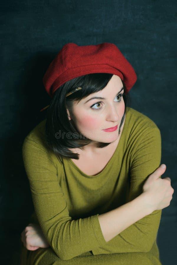 Kobieta w zieleń smokingowym i czerwonym berecie na czarnym ściennym tle fotografia royalty free
