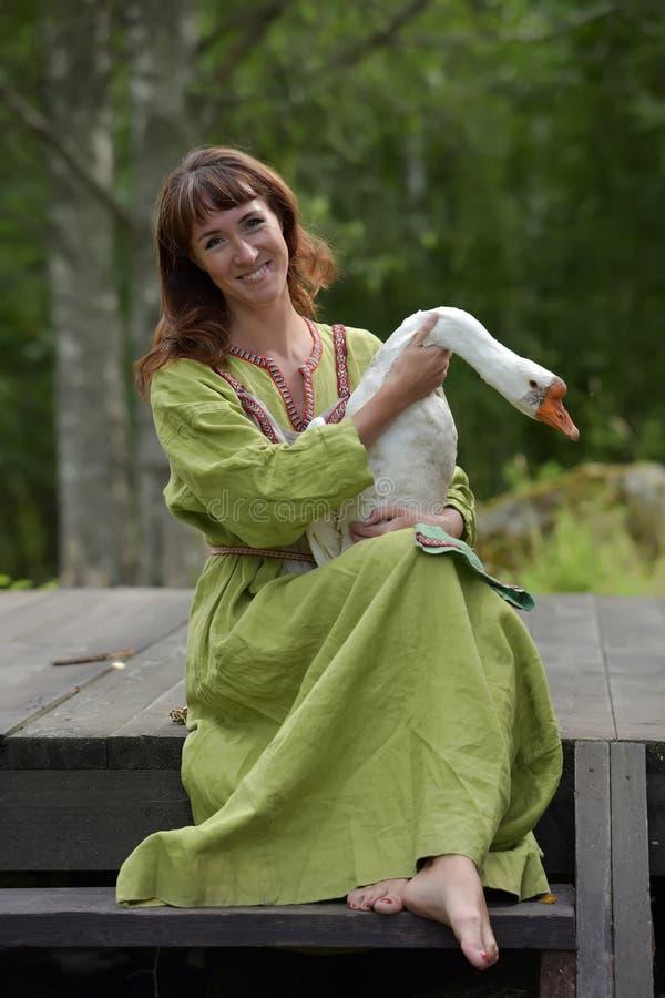Kobieta w zieleni sukni z g?sk? w ona r?ki obraz royalty free