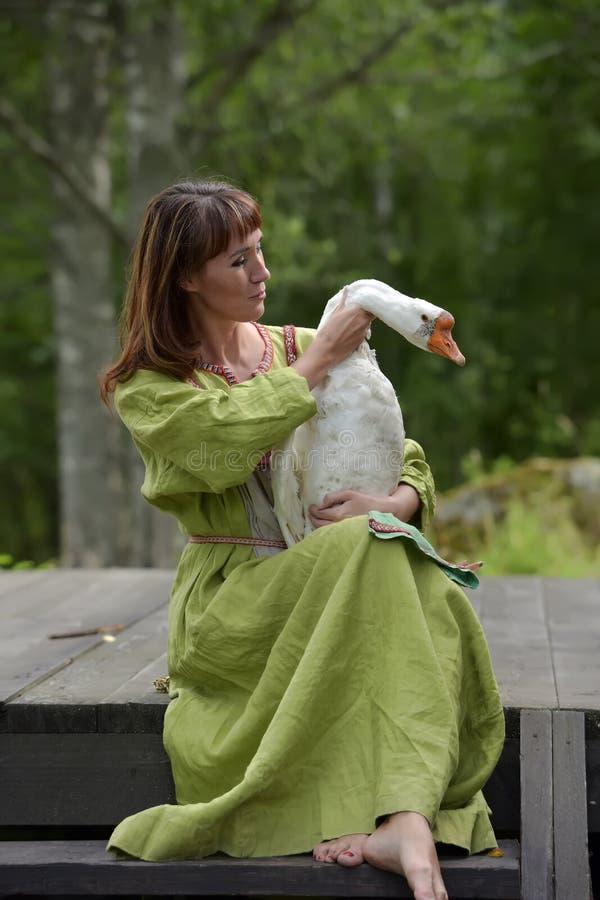 Kobieta w zieleni sukni z g?sk? w ona r?ki obrazy royalty free