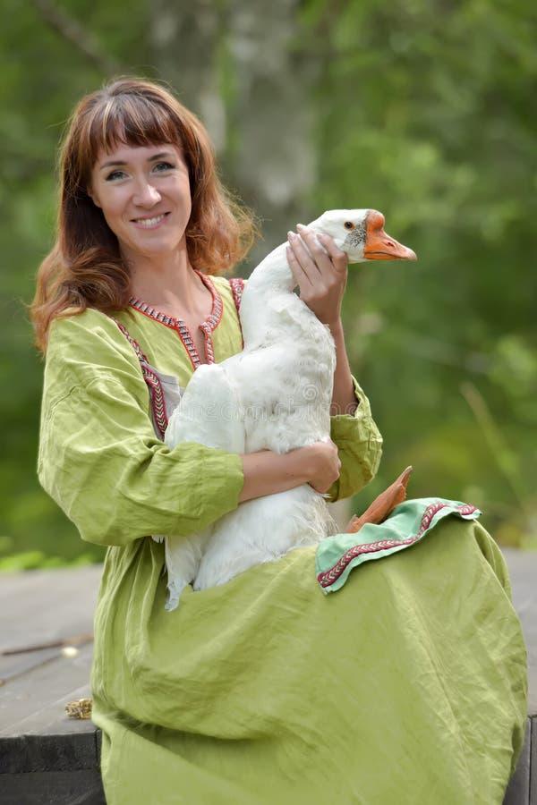 Kobieta w zieleni sukni z g?sk? w ona r?ki zdjęcie stock
