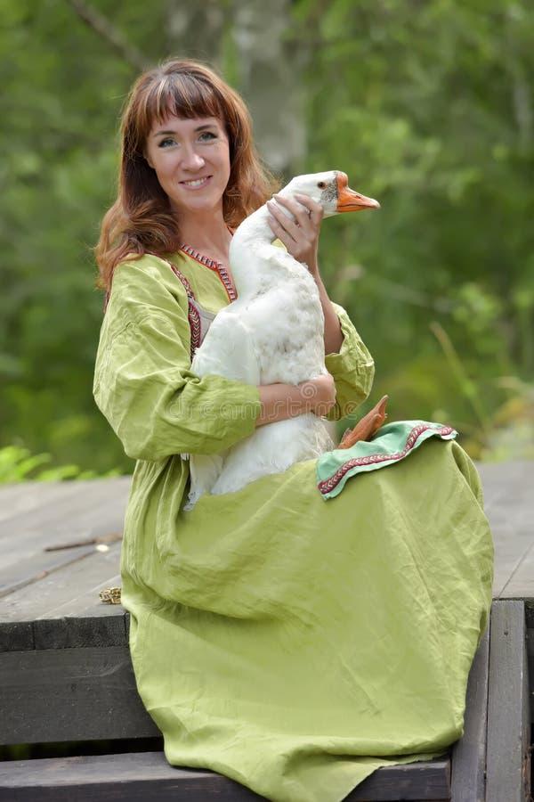 Kobieta w zieleni sukni z g?sk? w ona r?ki fotografia royalty free