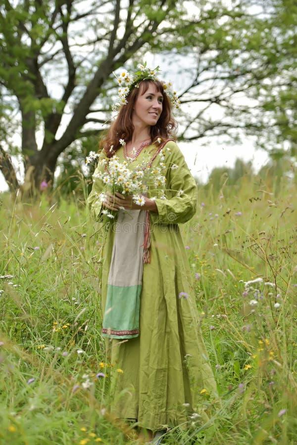 Kobieta w zielonej sukni z wiankiem stokrotki w jej w?osy i bukietem stokrotki w jej r?kach zdjęcia royalty free