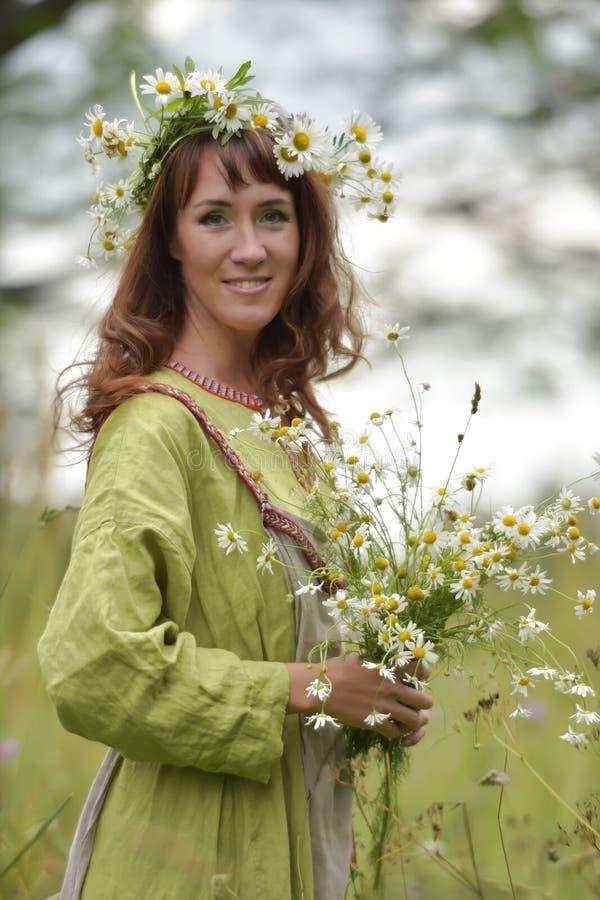 Kobieta w zielonej sukni z wiankiem stokrotki w jej w?osy i bukietem stokrotki w jej r?kach fotografia stock