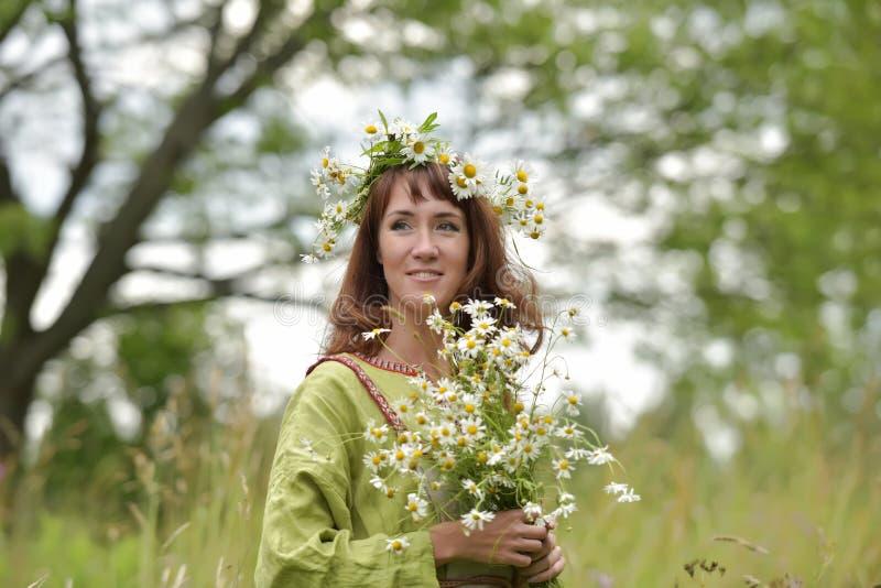 Kobieta w zielonej sukni z wiankiem stokrotki w jej włosy i bukietem stokrotki w jej rękach obrazy stock