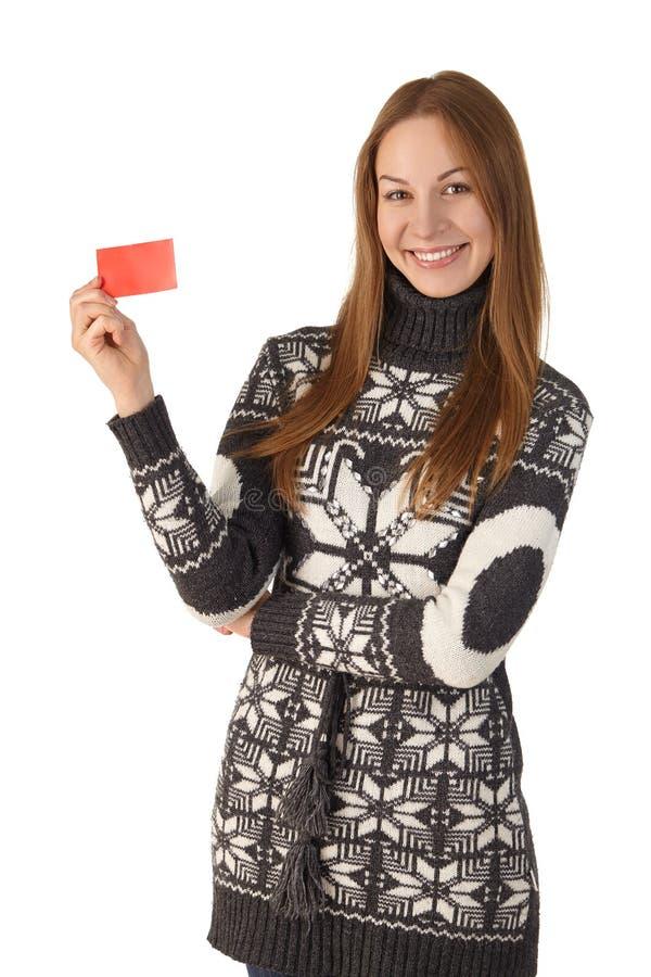 Kobieta w zima puloweru uśmiechniętej pozyci z kartą zdjęcia royalty free