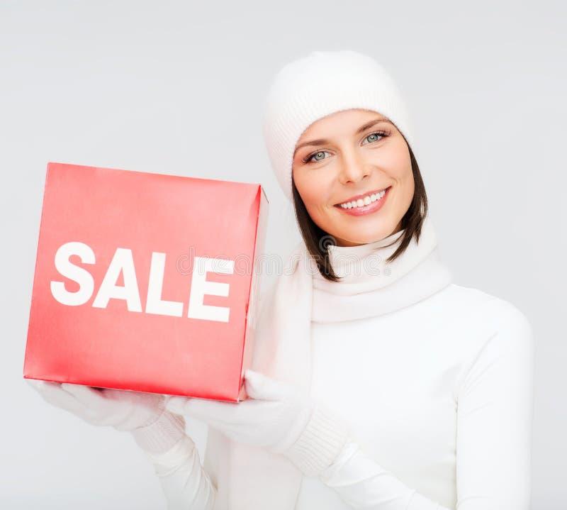 Kobieta w zimie odziewa z czerwonym sprzedaż znakiem