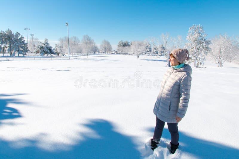 Kobieta w zimy parkowej cieszy się pogodnej pogodzie zdjęcia stock