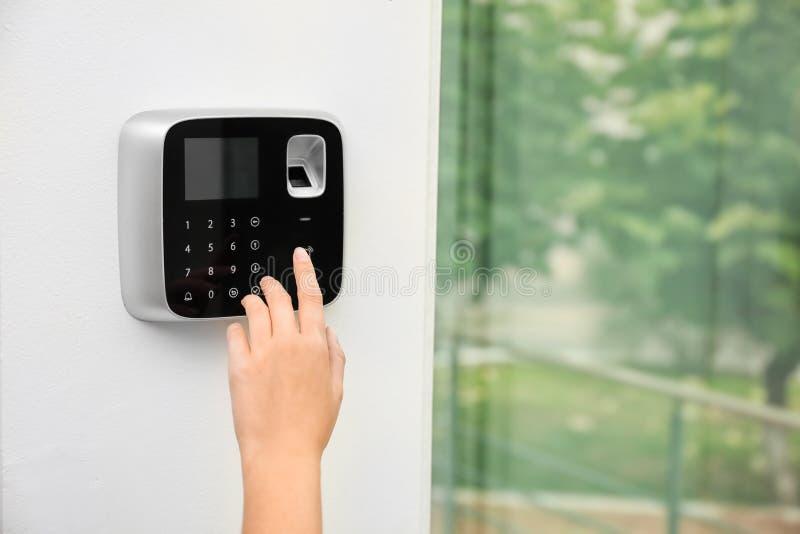 Kobieta wchodzić do kod na alarmowego systemu klawiaturze indoors fotografia stock